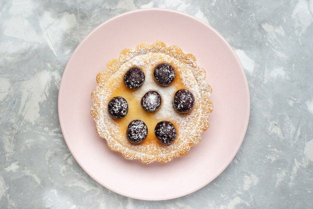 Вид сверху сахарного торта с фруктами внутри тарелки на светлом столе, фруктовая выпечка, сахар, сладкое печенье