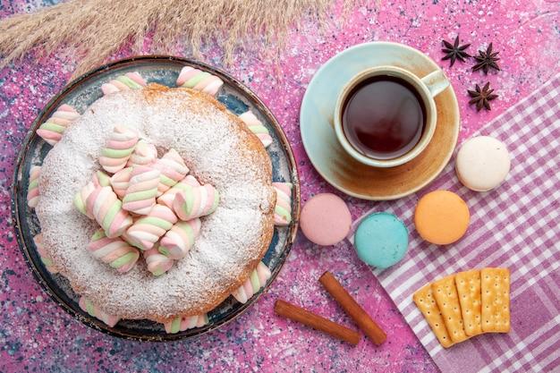 Vista dall'alto della torta di zucchero a velo con macarons e tazza di tè sulla superficie rosa