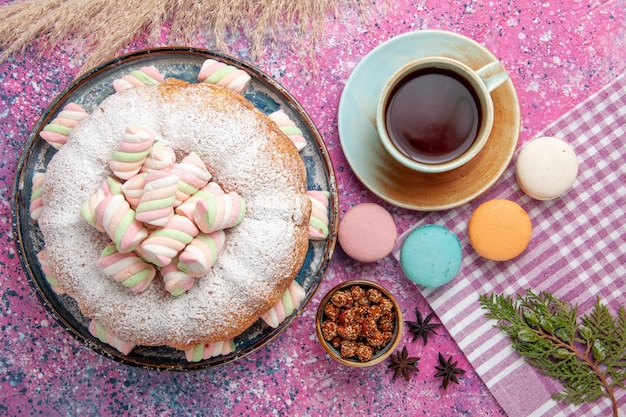 Top view of sugar powdered cake with marshmallows and cup of tea on pink surface