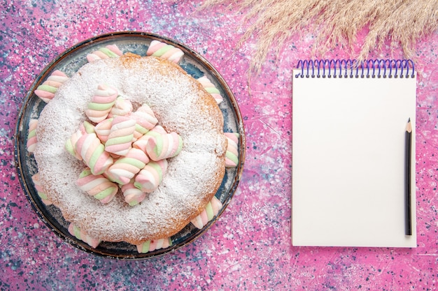 Top view of sugar powdered cake with sweet marshmallows and notepad on pink surface