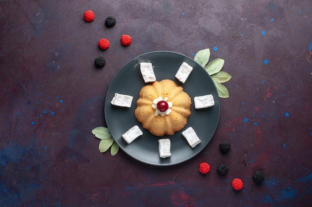Vista dall'alto di zucchero a velo caramelle delizioso torrone con torta e frutti di bosco confettura su superficie scura