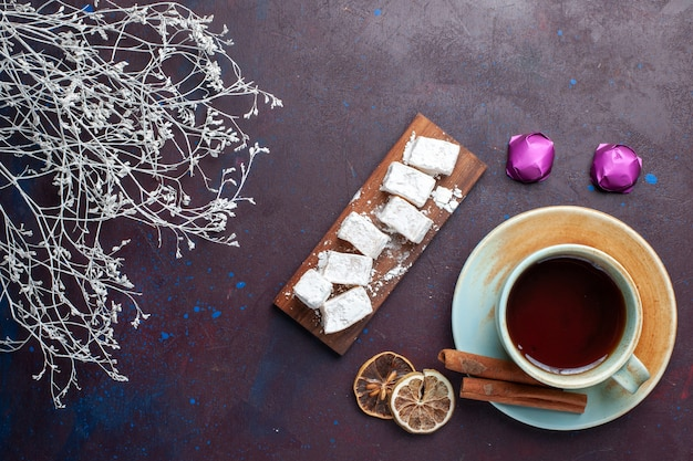 Top view of sugar powdered candies delicious nougat with cup of tea on the dark surface