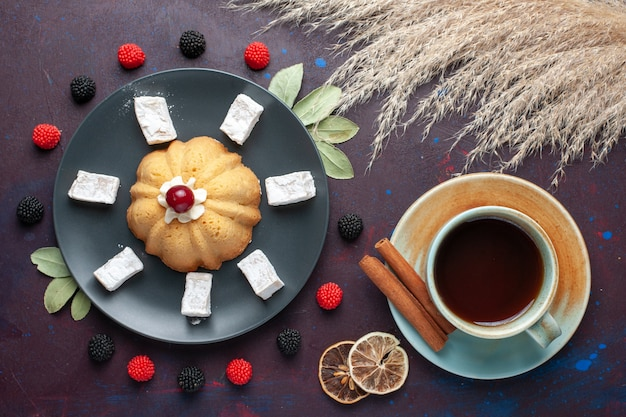Vista dall'alto di zucchero a velo caramelle delizioso torrone con torta di tè e frutti di bosco confettura su superficie scura