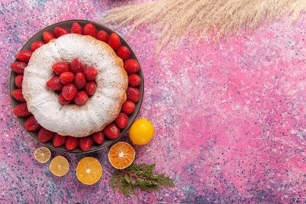 Вид сверху клубничный пирог с сахарной пудрой и лимоном на розовом