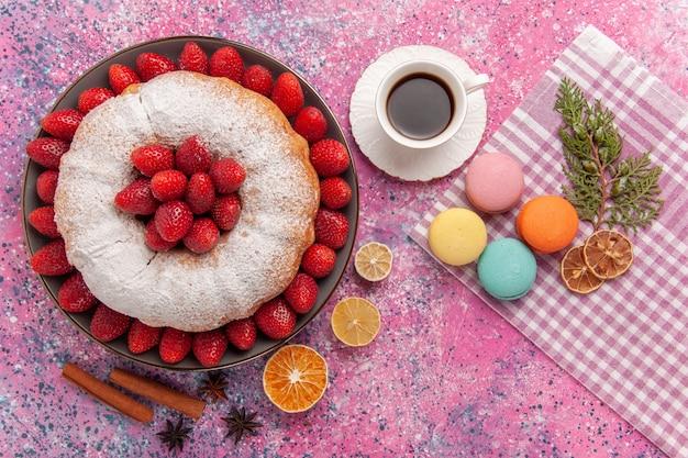 Vista dall'alto torta di fragole torta di zucchero in polvere con macarons su rosa chiaro