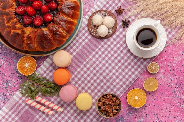 Vista dall'alto torta di fragole torta di zucchero in polvere con macarons sul rosa