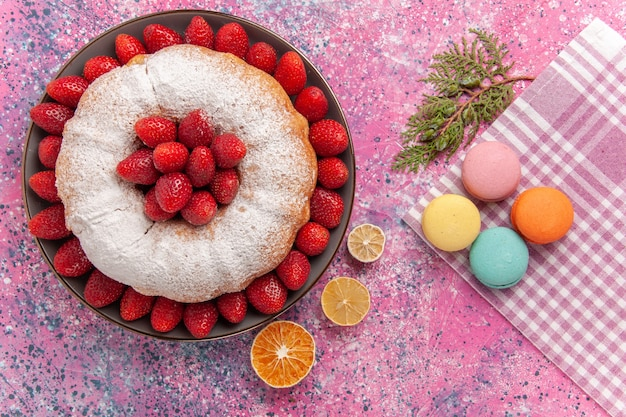 Top view sugar powdered pie strawberry cake with macarons on pink