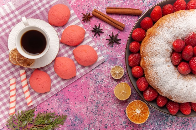 Vista dall'alto torta di fragole torta di zucchero in polvere con tè e torte sul rosa