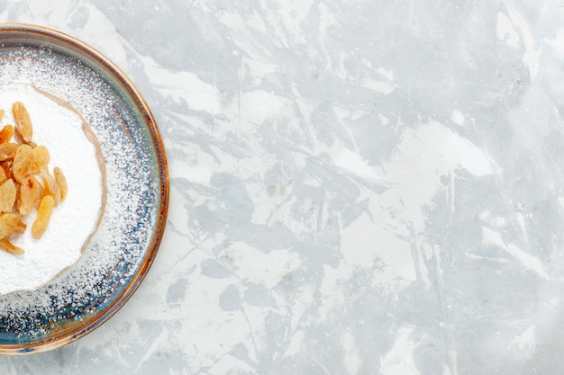 Vista dall'alto uvetta in polvere di zucchero uva secca all'interno del piatto sulla scrivania bianca
