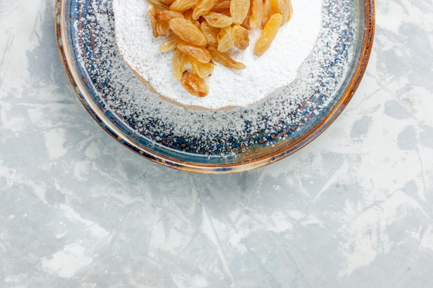 Vista dall'alto uvetta in polvere di zucchero uva secca sopra una piccola torta all'interno del piatto sulla scrivania bianca