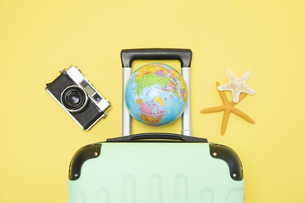 Top view of a suitcase, globe, camera and starfishes on a yellow background - vacation concept