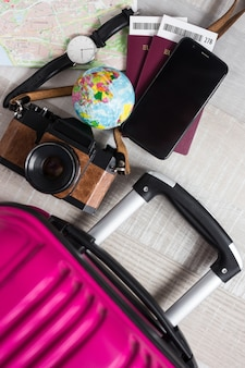 Top view of suitcase passports tickets map smart phone wristwatch and vintage camera