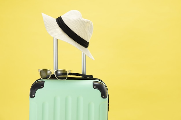 Top view of a suitcase, sunglasses, camera and hat on a yellow background - vacation concept