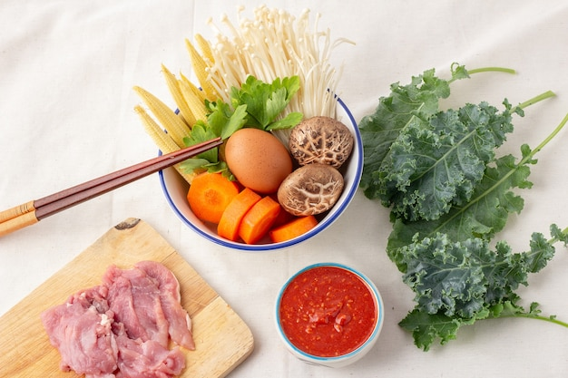 Top view of sukiyaki set, many vegetables in white bowl include carrots, baby corn, shiitake mushrooms, golden needles, celery and chicken eggs, raw pork on cutting board, kale on a white tablecloth.