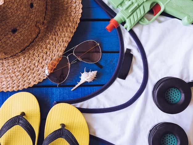 Top view of summer accessories on blue wooden floor.