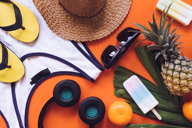 Top view of summer accessories on orange background