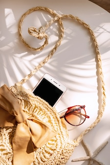 Top view of summer bag , smart phone and sunglasses on white color wall, travel concept. flat lay , copy space