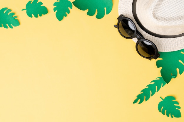 Top view of summer concept with sunglasses and hat on yellow background