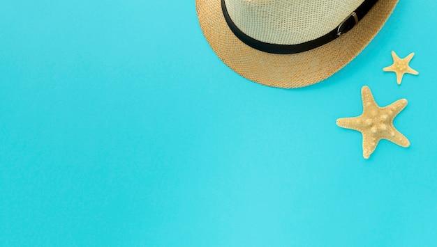 Вид сверху летняя шляпка и морская звезда с копией пространства