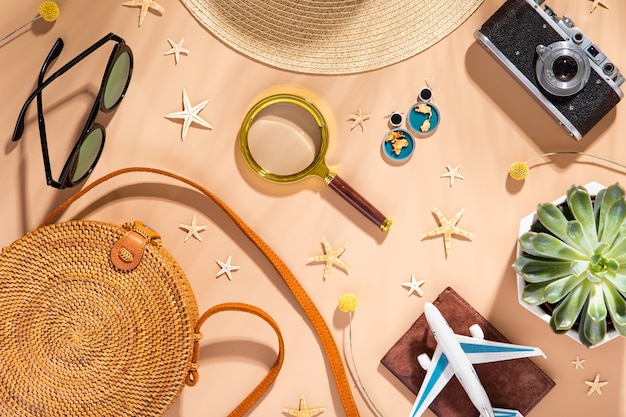 Top view of summertime accessories on natural tone background with palm leaf shadow, flat lay