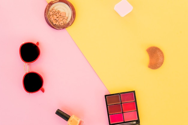Top view of sunglasses and beauty products on dual background