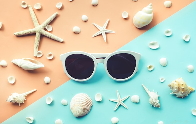 Top view of sunglasses and seashell set on color background.
