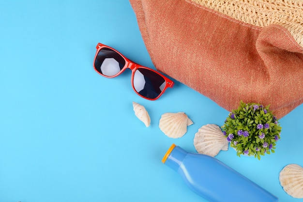Top view of sunglasses, shells, starfish and sunblock