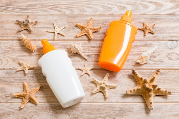 Top view of sunscreen bottle with seashells and starfish on wooden board background with copy space. flat lay concept of summer travel vacation