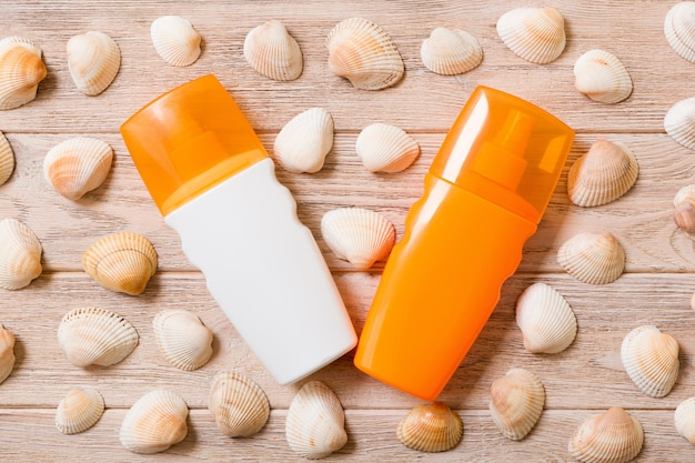 Top view of sunscreen bottle with seashells on wooden board background with copy space. flat lay concept of summer travel vacation.