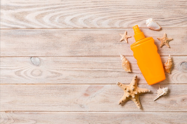 Top view of sunscreen bottle with starfish on wooden board background with copy space. flat lay concept of summer travel vacation.