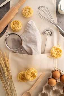 Top view supplies with pasta and ingredients in apron