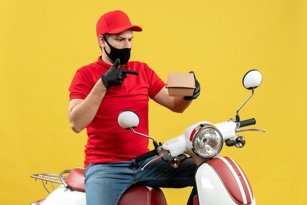 Vista superiore del ragazzo di consegna confuso sorpreso che indossa guanti di camicetta e cappello rossi in maschera medica che si siede sullo scooter che mostra l'ordine