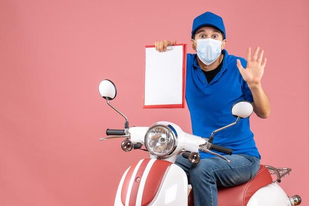 Vista dall'alto del corriere sorpreso in maschera medica che indossa un cappello seduto su uno scooter che tiene un documento su una pesca pastello