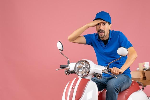 Vista dall'alto del corriere sorpreso che indossa un cappello seduto su uno scooter che consegna ordini su pesca pastello