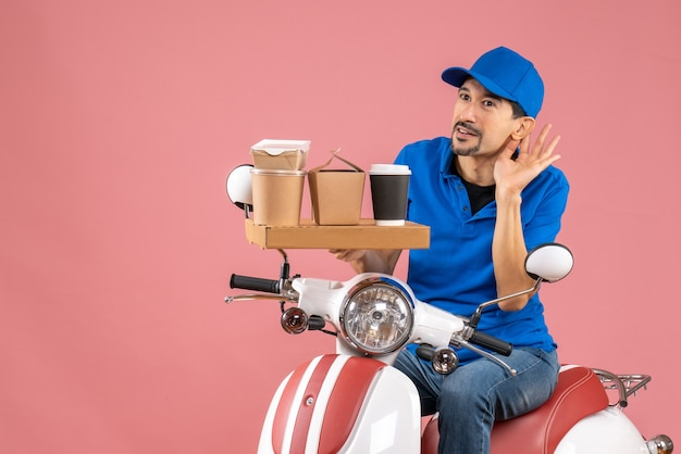 Vista dall'alto del corriere sorpreso che indossa un cappello seduto su uno scooter ascoltando l'ultimo spettegolare sulla pesca pastello