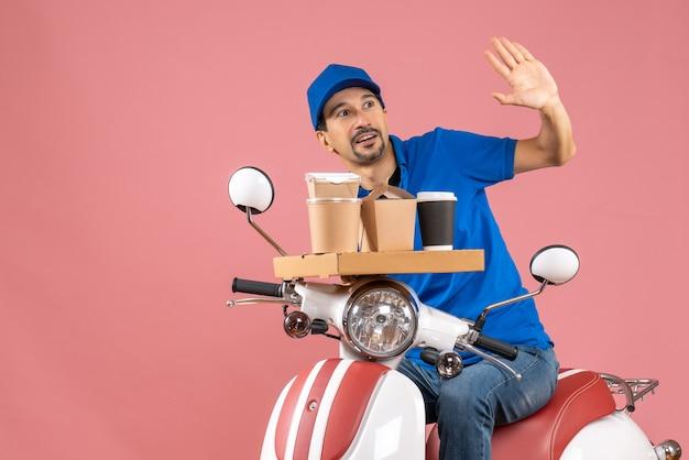 Vista dall'alto del corriere sorpreso che indossa un cappello seduto su uno scooter che saluta qualcuno su una pesca pastello