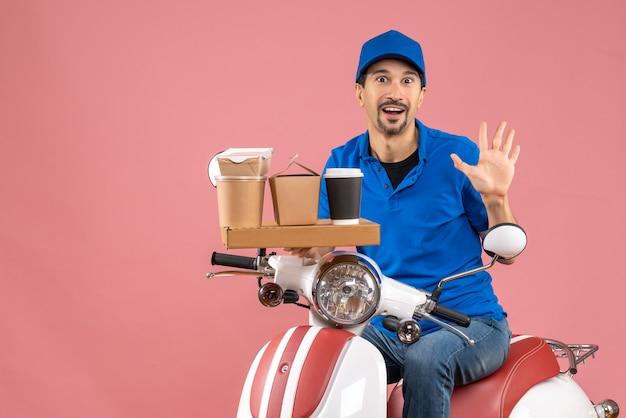 Vista dall'alto del corriere sorpreso che indossa un cappello seduto su uno scooter che mostra cinque su una pesca pastello