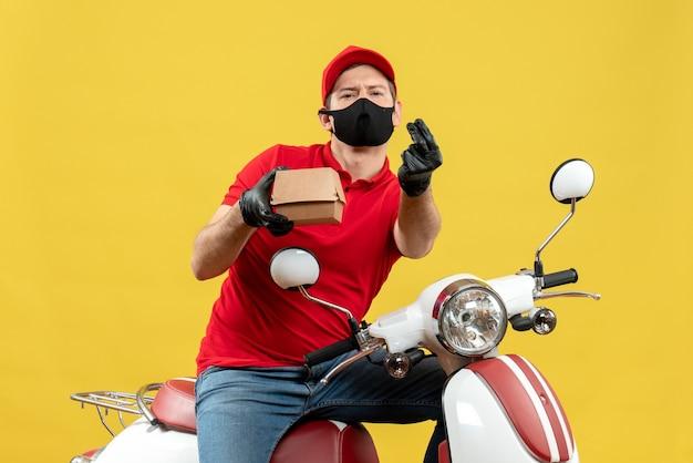 Vista superiore dell'uomo sorpreso del corriere che indossa guanti rossi della camicetta e del cappello nella mascherina medica che si siede sull'ordine della tenuta dello scooter