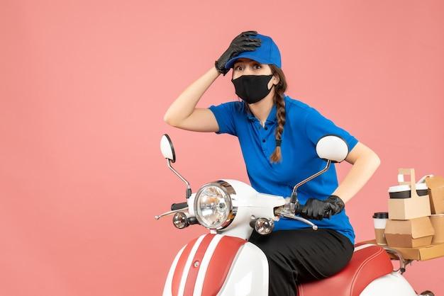 Vista dall'alto della donna corriere sorpresa che indossa maschera medica e guanti seduti su uno scooter che consegna ordini su pesca pastello
