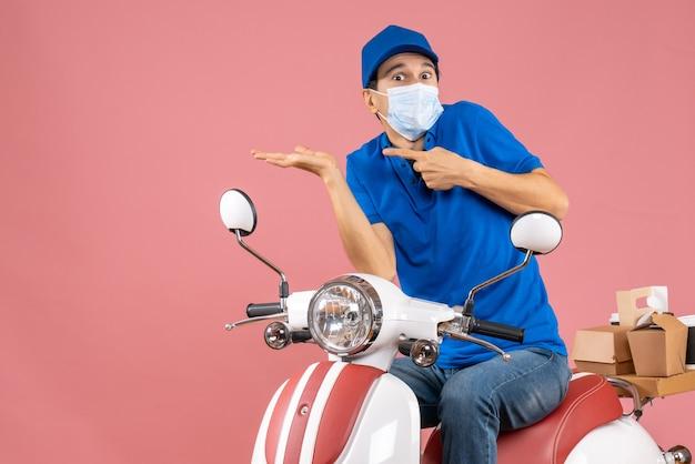Vista dall'alto del ragazzo delle consegne sorpreso in maschera medica che indossa un cappello seduto su uno scooter su una pesca pastello
