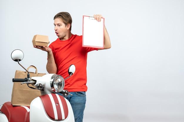 Vista dall'alto del fattorino sorpreso in uniforme rossa in piedi vicino a scooter tenendo l'ordine e il documento sul muro bianco