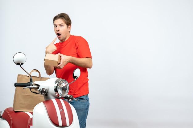 Vista dall'alto del fattorino sorpreso in uniforme rossa in piedi vicino a scooter sul muro bianco