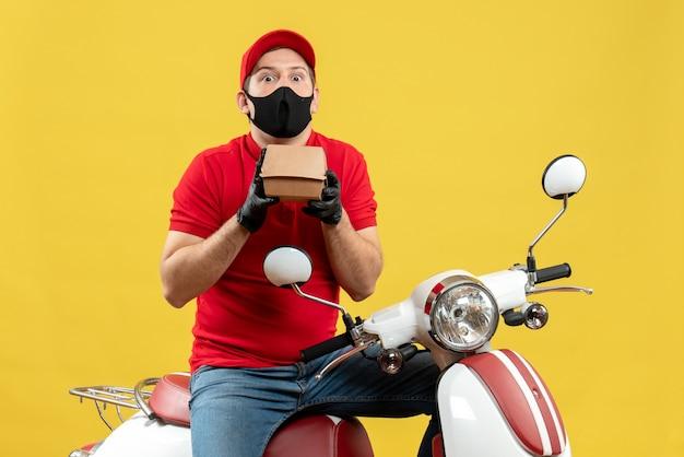 Vista superiore del fattorino sorpreso che indossa guanti di camicetta e cappello rossi in maschera medica che si siede sullo scooter che mostra l'ordine