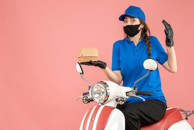 Vista dall'alto del fattorino sorpreso che indossa maschera medica e guanti seduto su uno scooter che consegna ordini su pesca pastello
