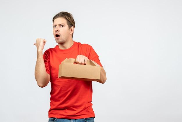 Vista dall'alto del giovane sorpreso ed emotivo in camicia rossa che tiene la scatola che punta indietro sul muro bianco