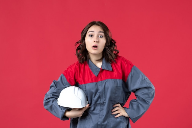 Vista dall'alto del costruttore femminile sorpreso in uniforme e che tiene elmetto su sfondo rosso isolato