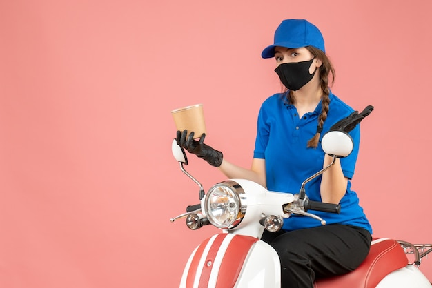 Vista dall'alto del corriere femminile sorpreso che indossa maschera medica e guanti seduto su uno scooter che consegna ordini su pesca pastello