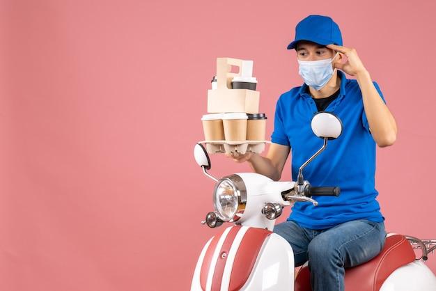 Vista dall'alto del fattorino maschio sorpreso in maschera con cappello seduto su uno scooter che consegna ordini su pesca orders