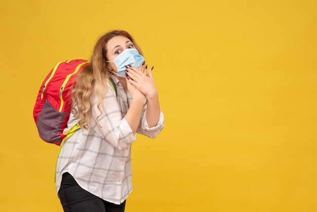 Top view of surprised travelling girl wearing her mask and backpack on yellow