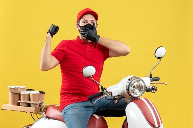 Vista superiore del giovane adulto sorpreso che indossa la camicetta rossa e guanti del cappello nella mascherina medica che trasporta l'ordine che si siede sullo scooter che indica indietro sulla parete gialla